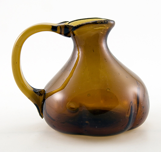 Early American free blown glass jug with bow handle.
